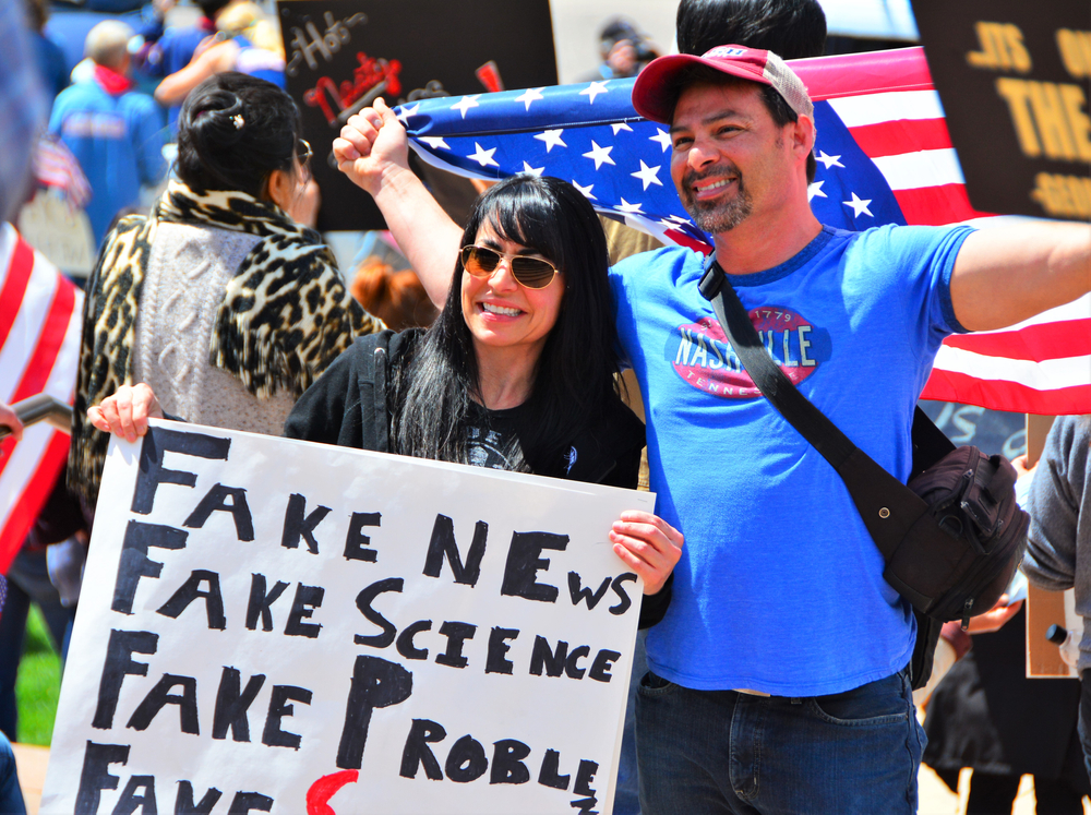 """Two people protesting stay at home measures in Denver, Colorado smiling, holding the American flag, with a sign that says """"fake news,"""" """"fake science,"""" """"fake problem"""""""